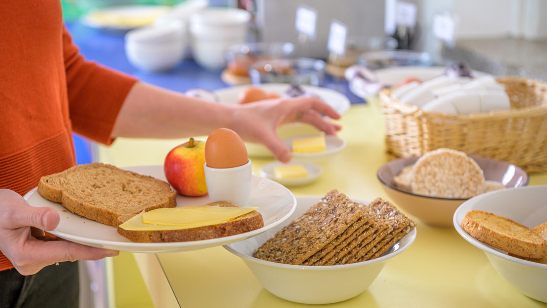 Ontbijt buffet beschuit crackers rijstewafel bord lopen broodje kaas fruit