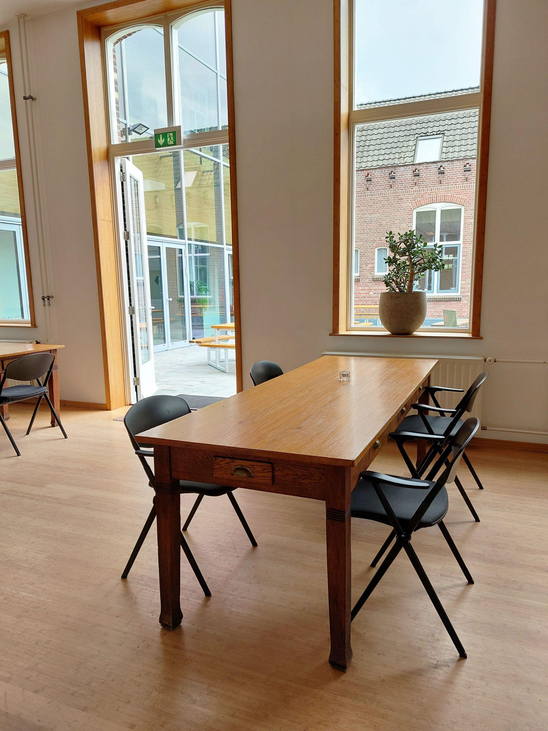 Foyer openslaande deuren tafel stoelen samen plant in ramen openslaande deur